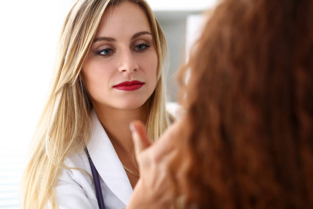 Beautiful female medicine doctor with serious face examine patie stock photo