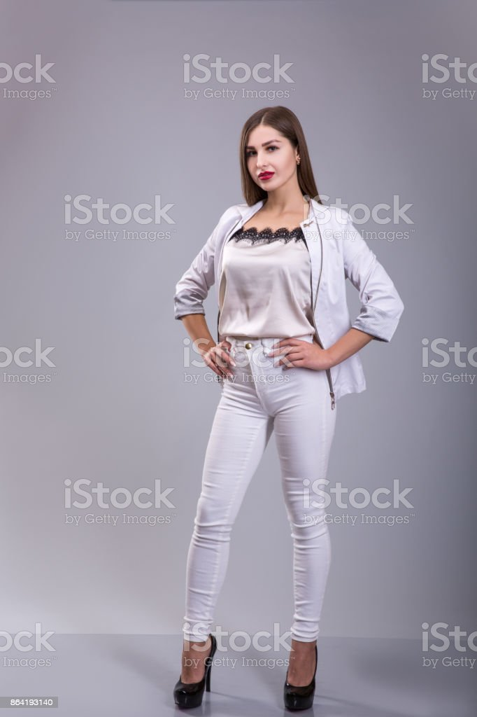 Beautiful female model dressed in white over gray background royalty-free stock photo