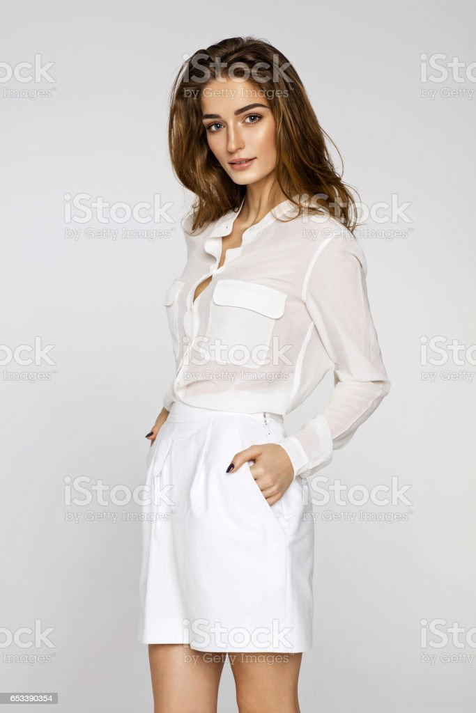 Beautiful female model posing in white clothes stock photo