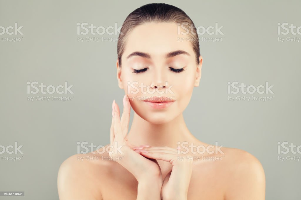 Beautiful Female Model with Healthy Skin and Closed Eyes. Perfect Face and Hand Closeup. Spa Beauty, Facial Treatment and Cosmetology Concept stock photo