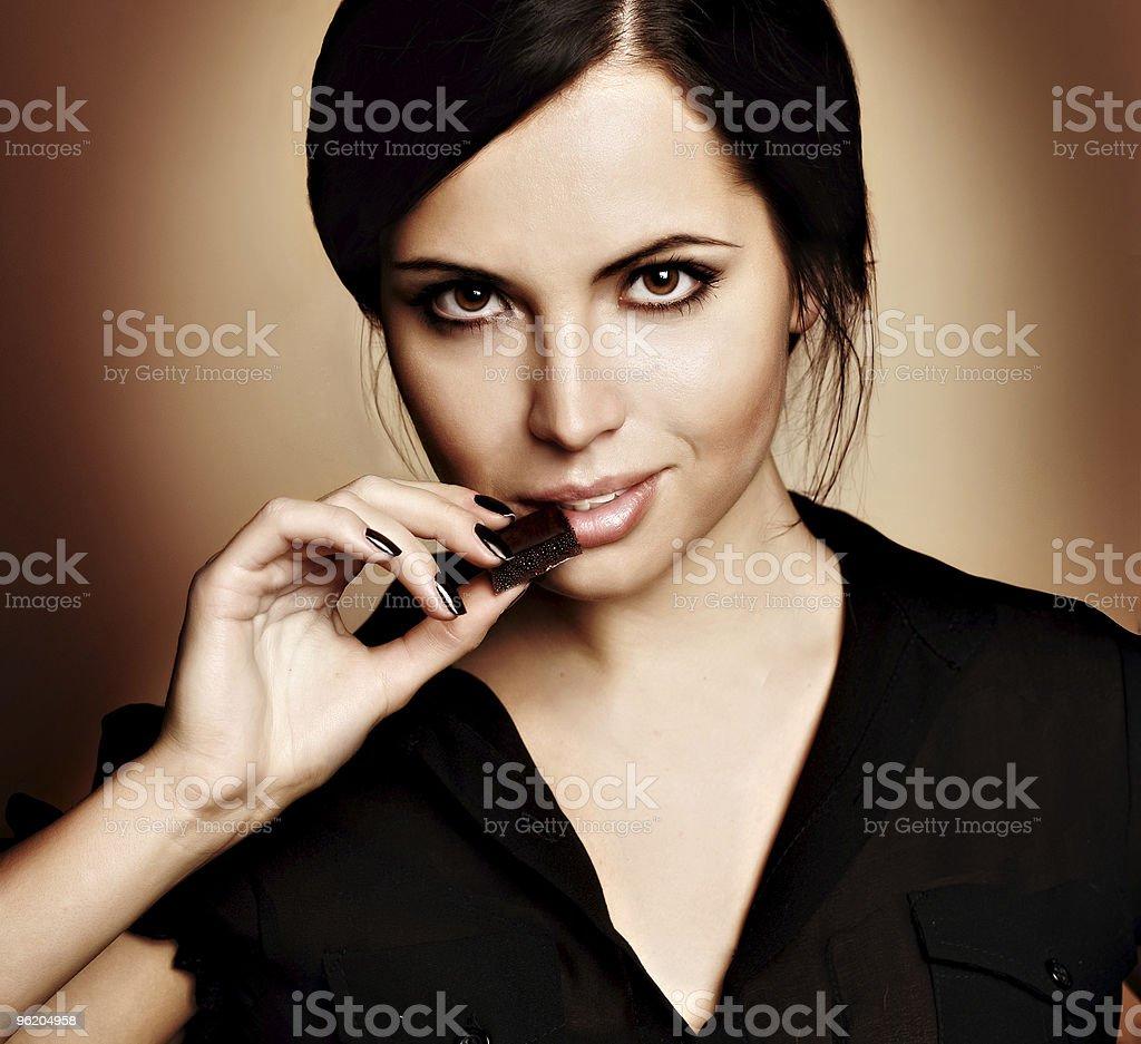 A beautiful female munching on chocolate stock photo