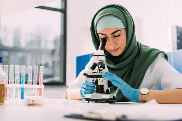 beautiful female muslim scientist looking through microscope during experiment in chemical laboratory - религиозная одежда стоковые фото и изображения