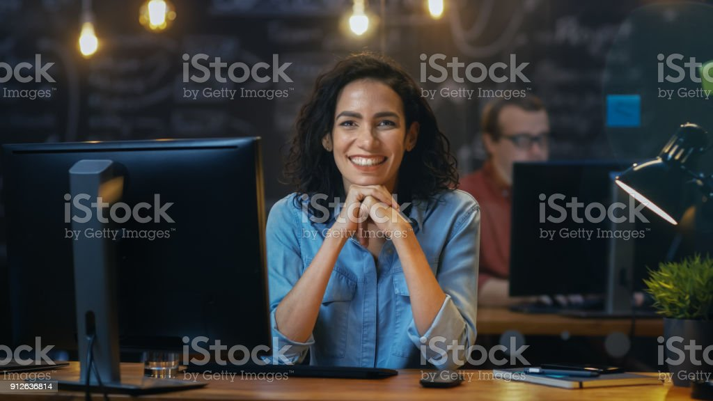 Beautiful Female Office Employee Works at Her Desk on a Personal Computer, She Interrupts Her Work and Smiles Charmingly for the Camera. In the Background  Coworker in the Creative Office. stock photo
