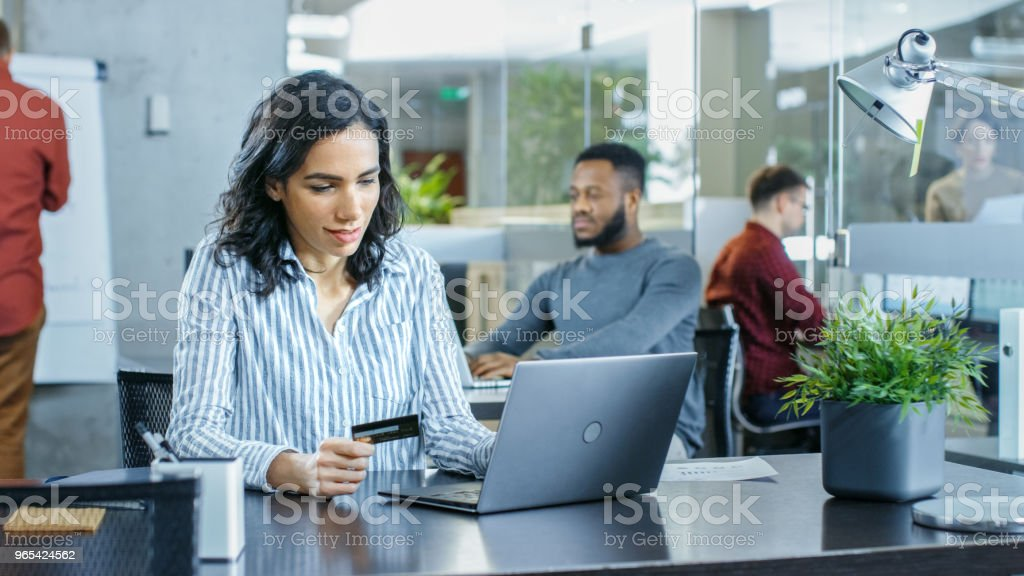 Beautiful Female Office Worker Makes Internet Purchase from Her Laptop Using Credit Card. In the Background Creative Young People Working. royalty-free stock photo