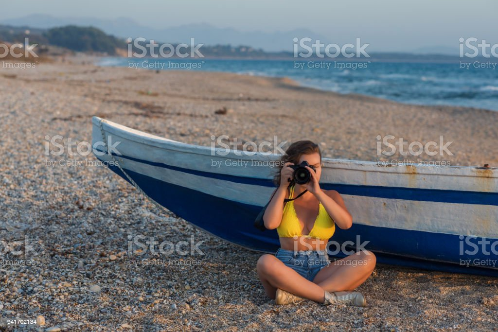 Beautiful female photographer in the bikini with professional camera near boat on the sand stock photo