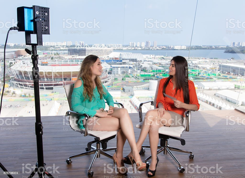 Beautiful female presenter interviewing a famous woman stock photo