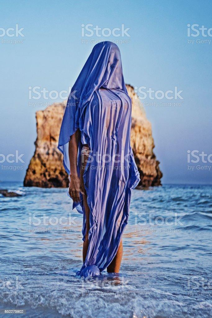 Beautiful female silhouette wearing a blue shroud on a rocky beach - fotografia de stock