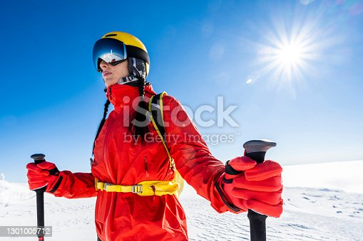 Young female skier fully equipped for a ski day in the mountain resort enjoys a divine winter day surrounded with snow and illuminated with sun beams.