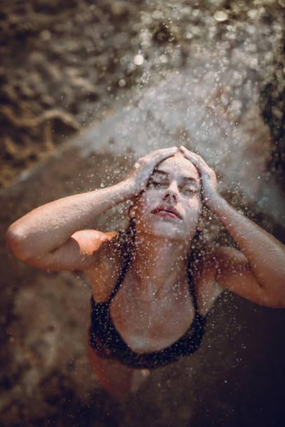 schöne weibliche spritzwasser, sand und wasser am strand - sonnendusche stock-fotos und bilder