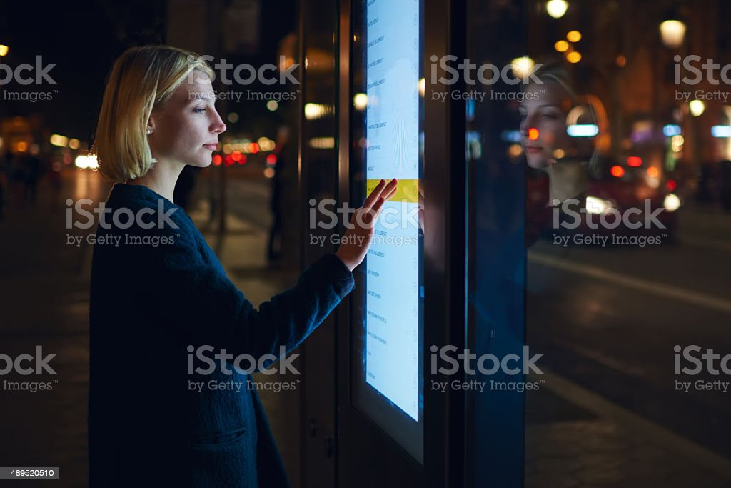 Beautiful female standing at big display which reflecting light bildbanksfoto