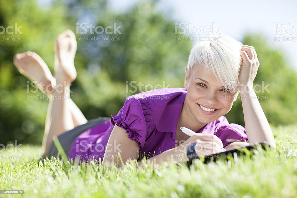 Beautiful female student is studying in a green field stock photo