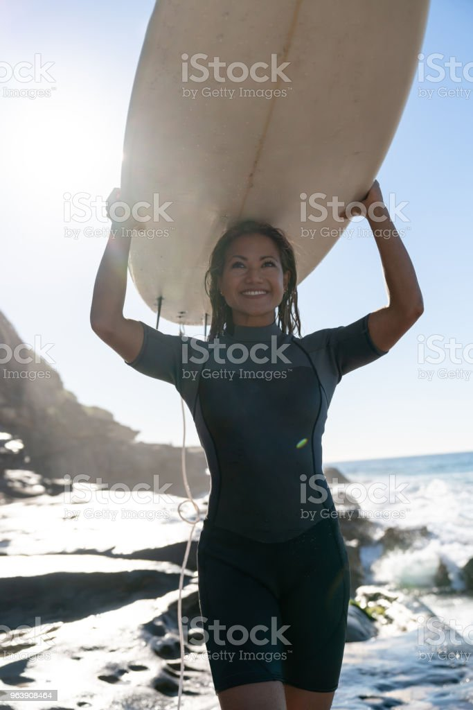 Beautiful female surfer carrying her board and looking very happy - Royalty-free Adult Stock Photo