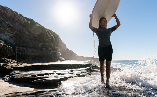 Beautiful Female Surfer Carrying Her Board Stock Photo - Download Image Now