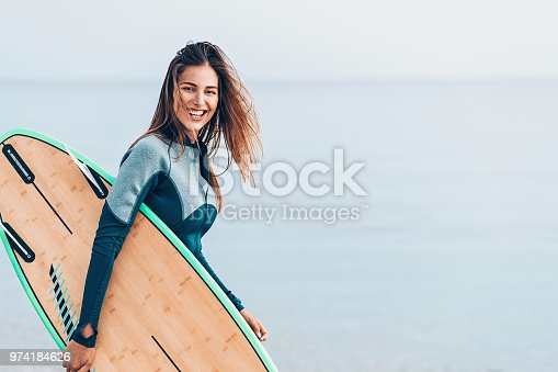 Surfer girl walking on the beach