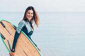 Surfer girl walking on the beach
