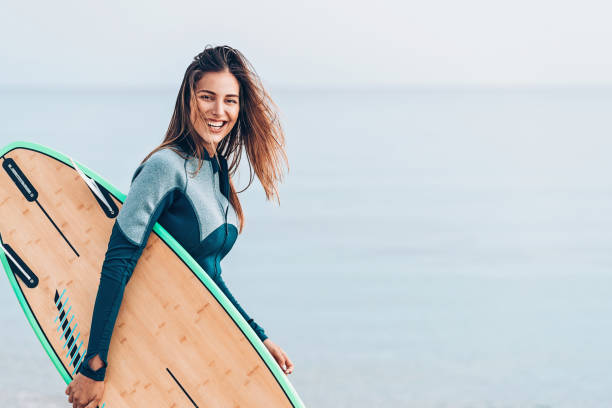 Beautiful female surfer, with copy space Surfer girl walking on the beach wetsuit stock pictures, royalty-free photos & images