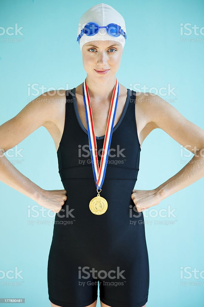Beautiful female swimmer with gold medal stock photo