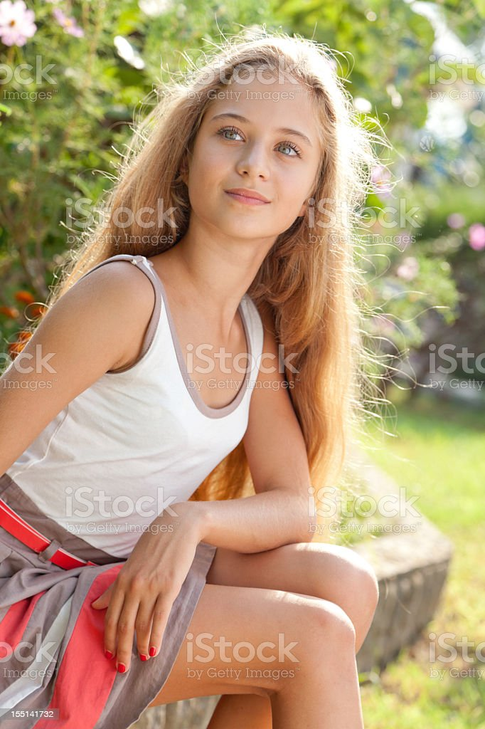 Beautiful female teenager sitting outdoors on curbs, posing, looking away stock photo