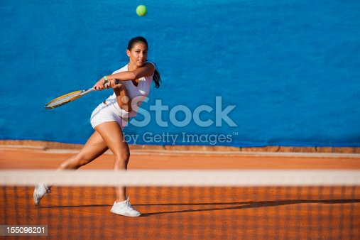 1153628111istockphoto Beautiful female tennis player on the blue background 155096201