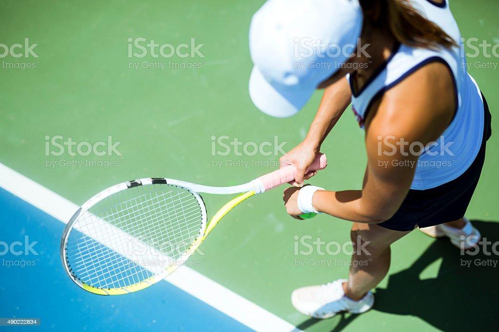 Beautiful female tennis player serving stock photo