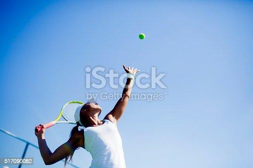 istock Beautiful female tennis player serving 517090082