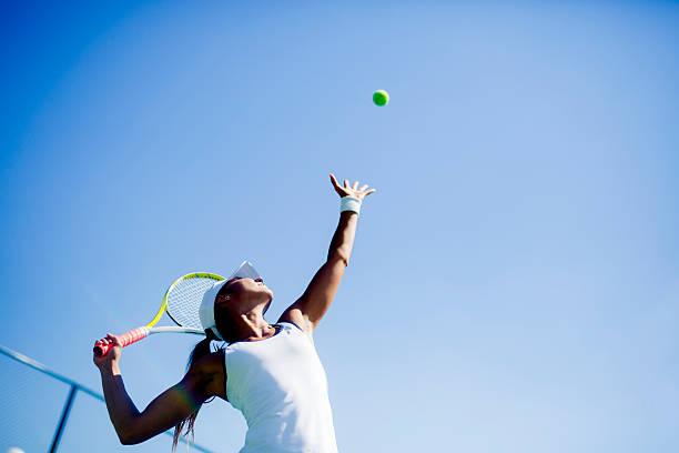 beautiful female tennis player serving - tennis stock pictures, royalty-free photos & images