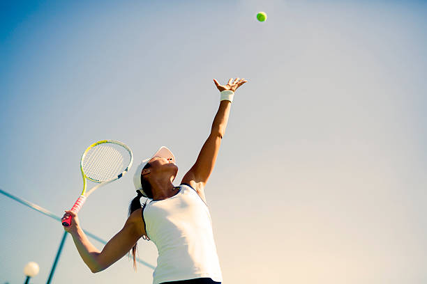 beautiful female tennis player serving - tennis stock photos and pictures