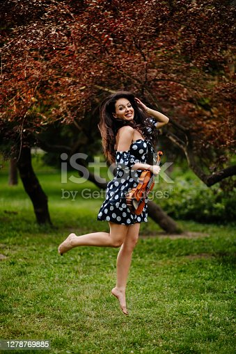 Beautiful female violinist holding a violin and having fun in the park