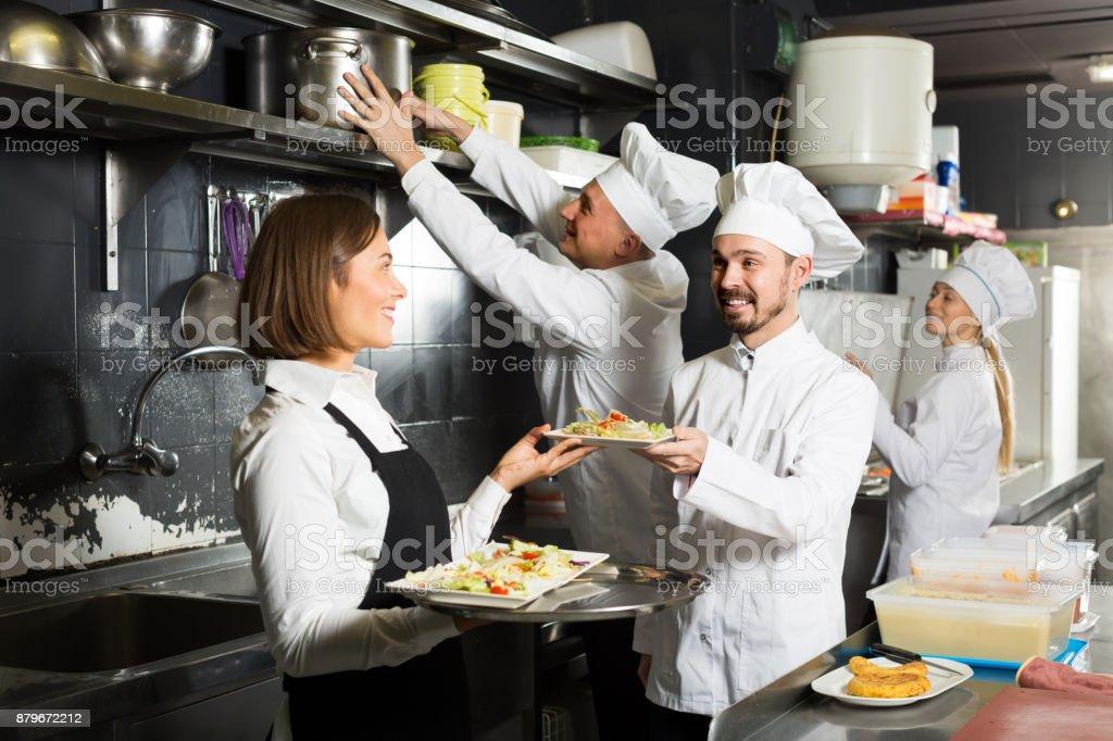 Belo garçom feminino tomando ordenou pratos - foto de acervo