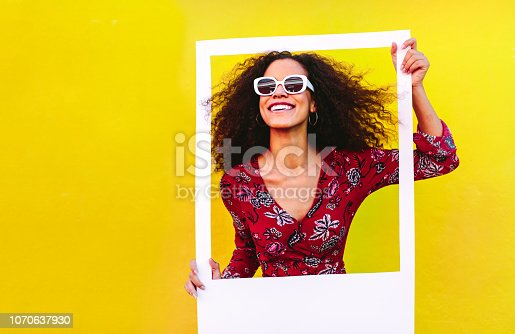 Mixed race woman with curly hair wearing sundress and sunglasses looking through blank photo frame. Beautiful female with big picture frame against yellow background.