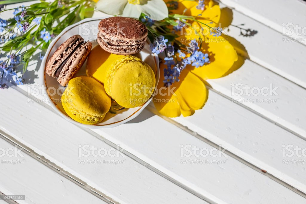 Beautiful feminine composition,bright colors. French macaroon sweets and tender flowers blossoms on white wooden background. 8 march, mothers day, Happy Easter. copy space. - Royalty-free Bakery Stock Photo