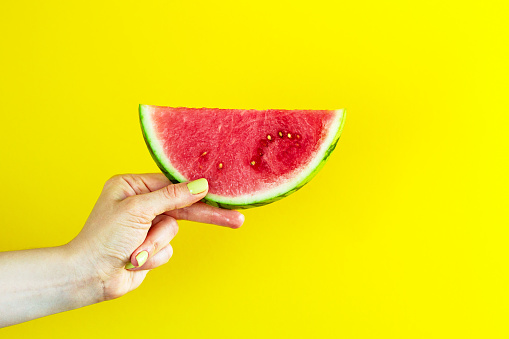Beautiful feminine hands holding fresh tasty red appetizing watermelon on bright yellow background. Summer Concept.
