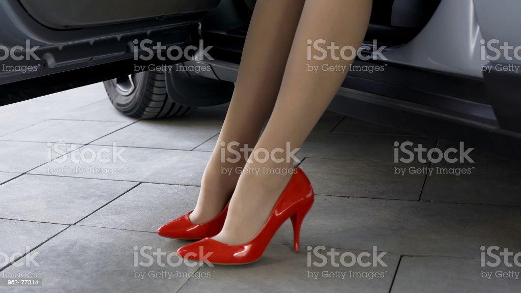 Schöne weibliche Modell mit roten hochhackigen Schuhen auf Fahrersitz im Auto sitzen – Foto