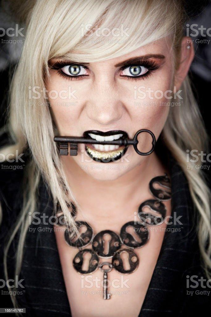 Beautiful, fierce blonde woman holding key royalty-free stock photo