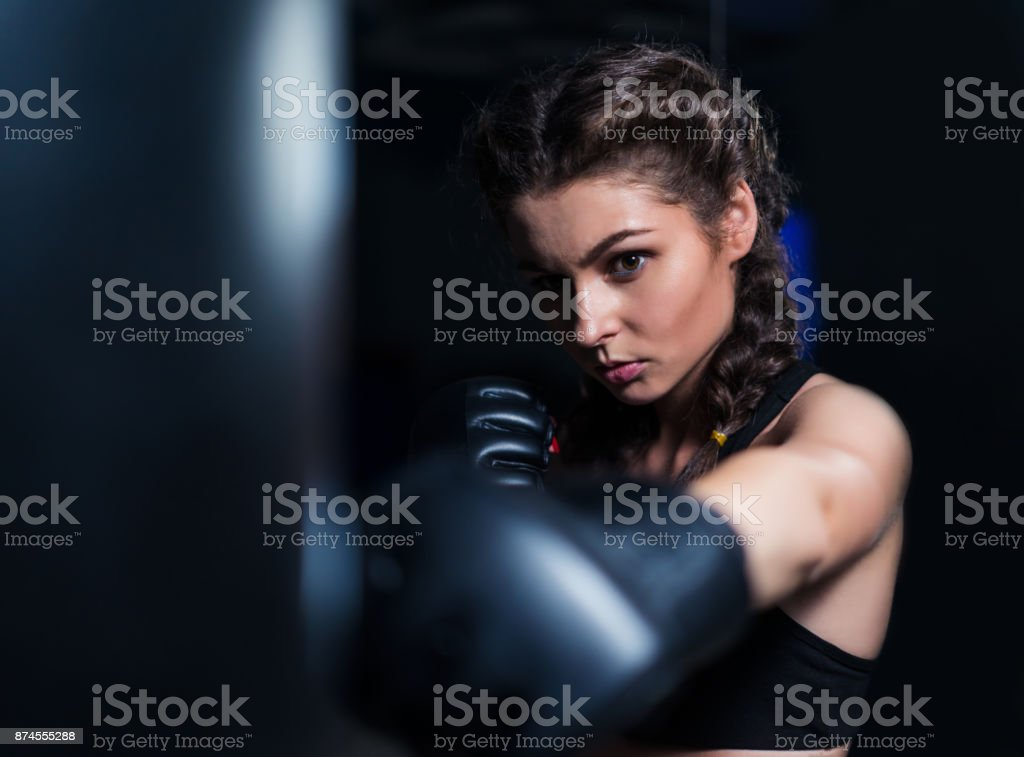 Beautiful  fighter boxer girl in training with heavy punching ba stock photo