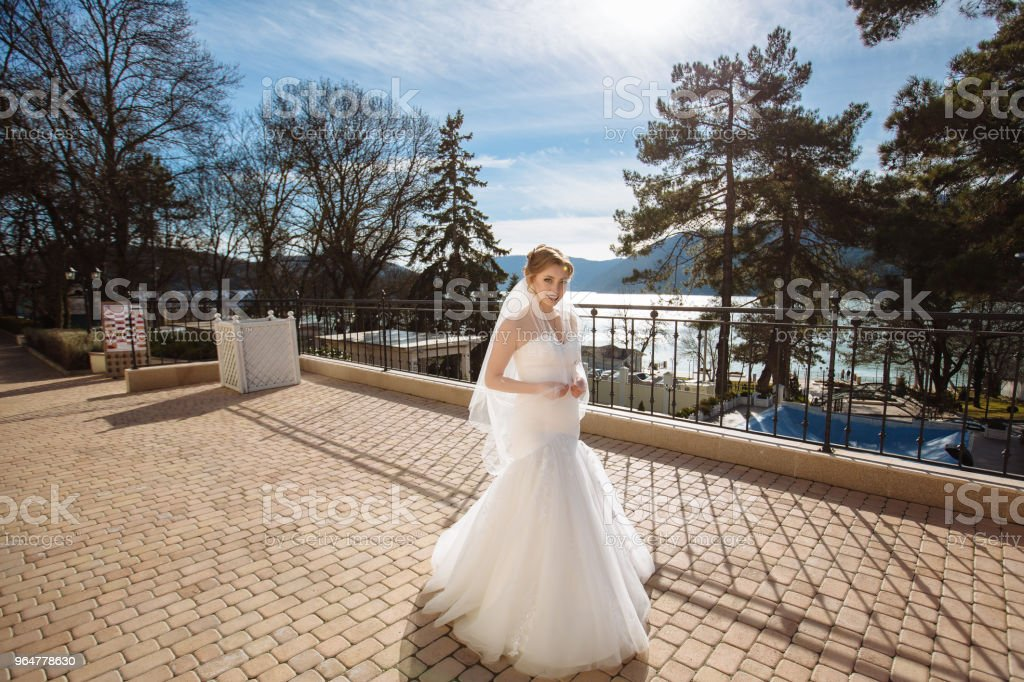 A beautiful figured bride strolls along the quay and admires the hills and the blue sunny sky royalty-free stock photo