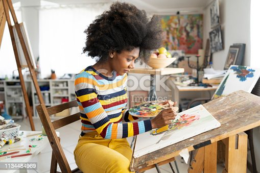 Beautiful fine art painter drawing in studio, holding color palette. Wears casual colorful clothes