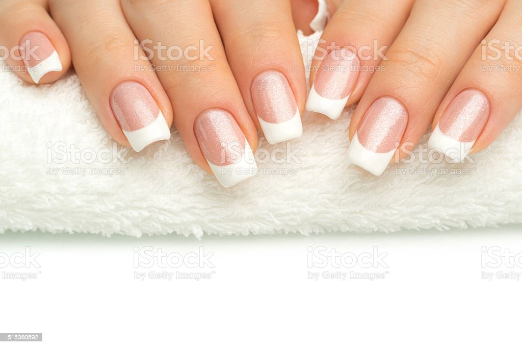 Beautiful fingers with french manicure on the towel. stock photo