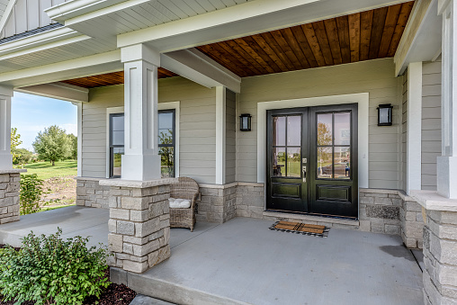 Siding, wood and stone make up the initial front entrance to the home