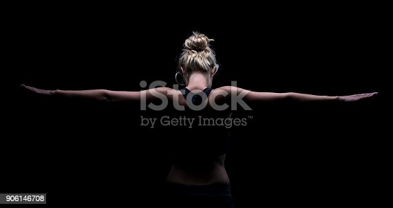 istock Beautiful fit and healthy blond woman in black top in the dark with arms stretched from behind 906146708