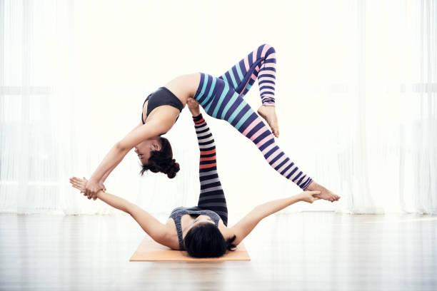 Beautiful fit flexible women practicing Acroyoga stock photo