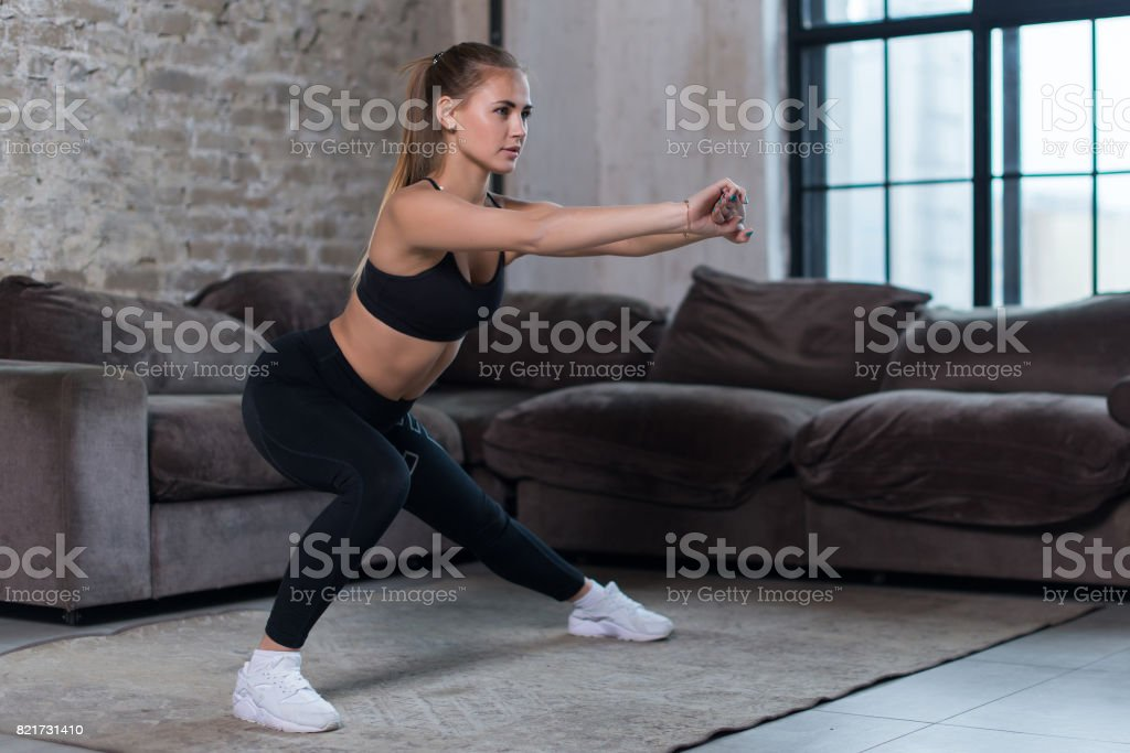 Beautiful fit girl doing home workout performing lateral lunges in a sitting room stock photo