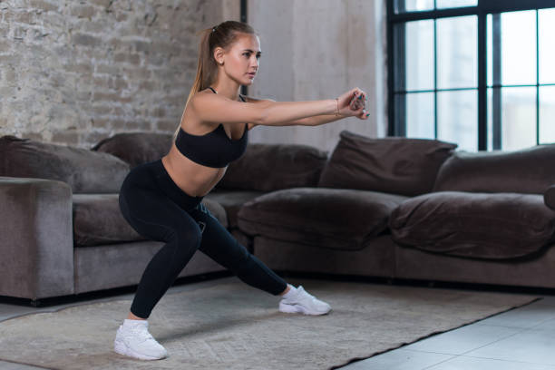 beautiful fit girl doing home workout performing lateral lunges in a sitting room - lunge stock photos and pictures