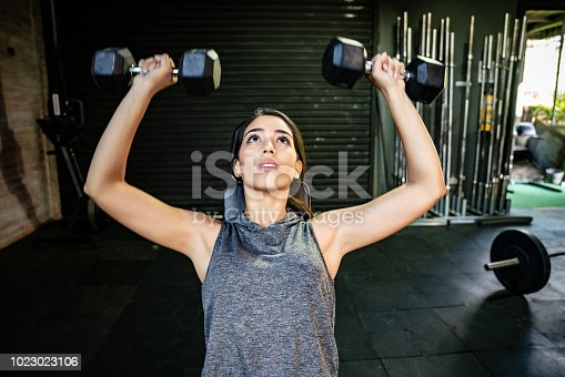Beautiful fit woman doing an arm workout with freeweights looking focused and determined