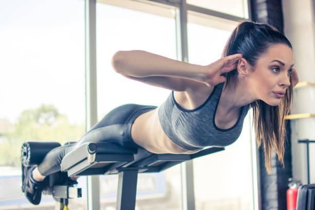 Schöne fit Frau tun Rückenverlängerung Übung auf Fitness-Gerät im Fitness-Studio – Foto