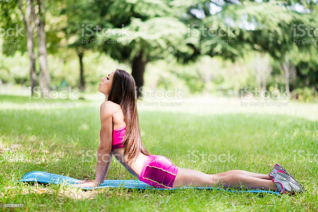 Beautiful Fit Woman Exercise by Doing Yoga in Nature stock photo