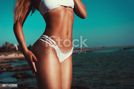istock Beautiful fit woman showing her tanned body on the beach 967142838
