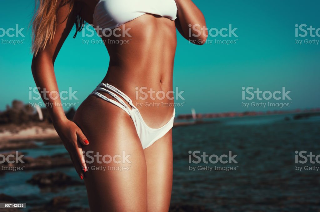 Beautiful fit woman showing her tanned body on the beach stock photo
