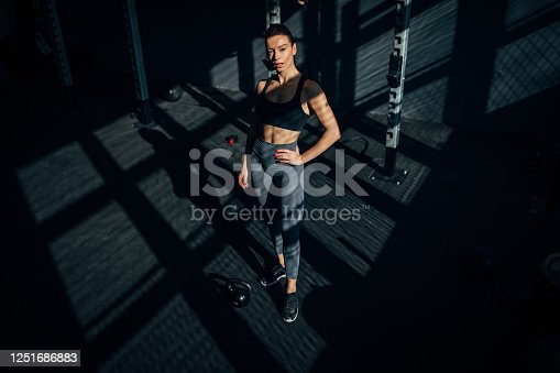 One beautiful fit young woman standing alone in the gym.
