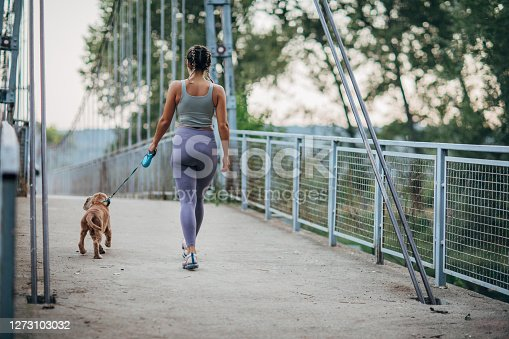 One woman, beautiful fit young woman, walking her dog on a small bridge in nature.